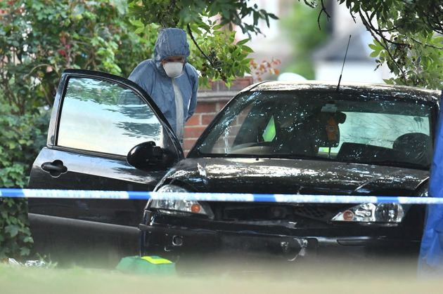 A forensic police officer examines a car at the scene in Lennard Road, Penge in south-east