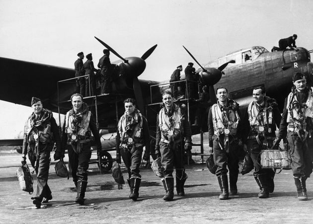 April 1943: The crew of a Lancaster bomber walk away from their plane after a flight while ground crew...