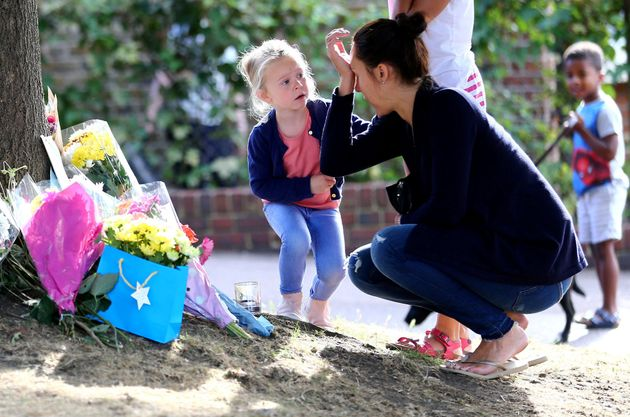 A woman is comforted by a child as she lays flowers at the