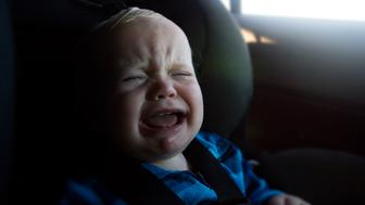A 12 month ld baby boy crying in his car seat.