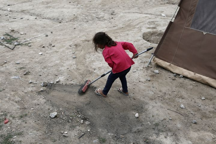 A small girl cleans up the area outside her tent in a makeshift refugee camp on the Greek-Macedonian border, on May 19, 2016.
