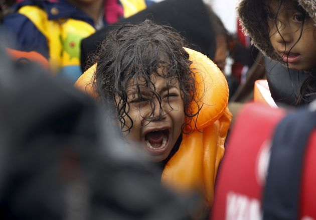 A Syrian refugee child screams inside an overcrowded dinghy after crossing part of the Aegean Sea from...