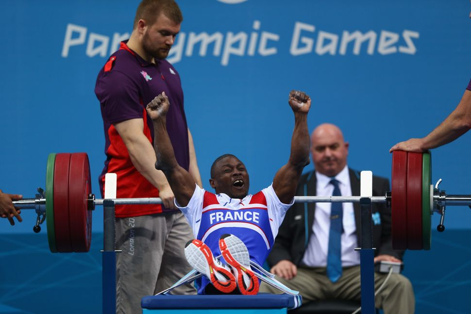 France's Patrick Ardon celebrates a successful lift in the men's 48-kilogram powerlifting in London.