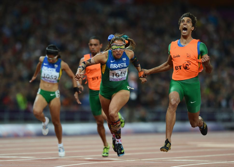 Terezinha Guilhermina of Brazil and guide Guilherme Soares de Santana cross the line to win gold in the women's 100-meter T11