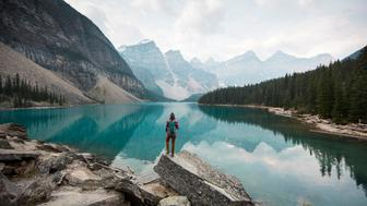 A woman standing on a scenic lookout overlooking Moraine Lake in Alberta, Canada.