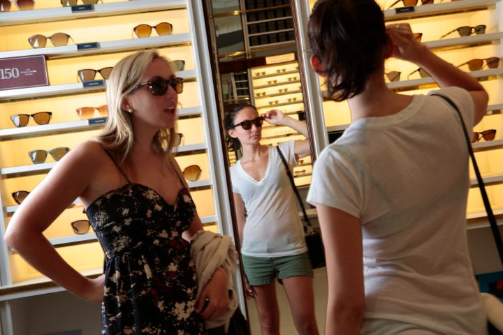 Two shoppers try on glasses at Warby Parker.