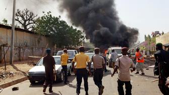Security personnel rush towards the site of a car bomb explosion near a stadium in the northeastern Nigerian city of Gombe February 2, 2015. The explosion occurred a few minutes after Nigerian President Goodluck Jonathan left a party rally at the stadium. A Reuters photographer said the bomb exploded, engulfing the car in flames and killing at least one bystander and wounding seven.     REUTERS/ Afolabi Sotunde (NIGERIA - Tags: DISASTER CIVIL UNREST CRIME LAW POLITICS TPX IMAGES OF THE DAY ELECTIONS)
