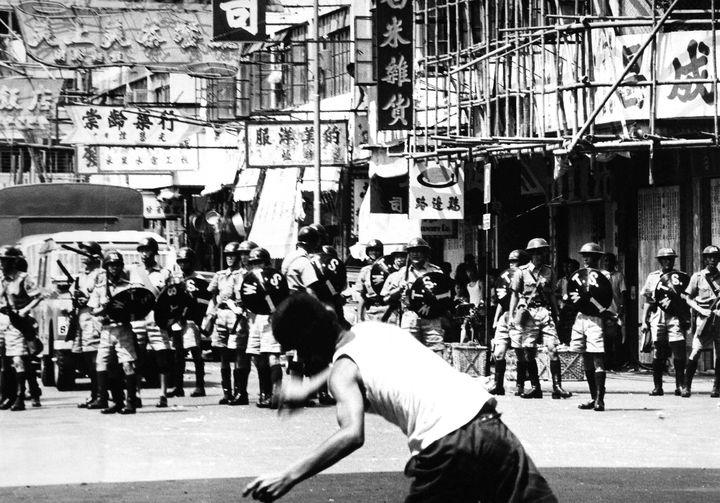 A rioter hurls a rock at police patrol during riots in Hong Kong, May 1967.