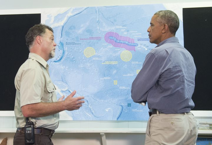 President Barack Obama, alongside refuge manager Bob Peyton, looks at a map of Midway Atoll in the Papahanaumokuakea Marine N