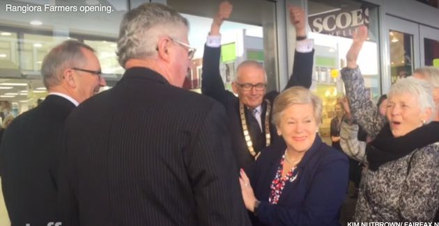 Waimakariri mayor David Ayers (c) raises his arms triumphantly at the openinrg of a new department store...