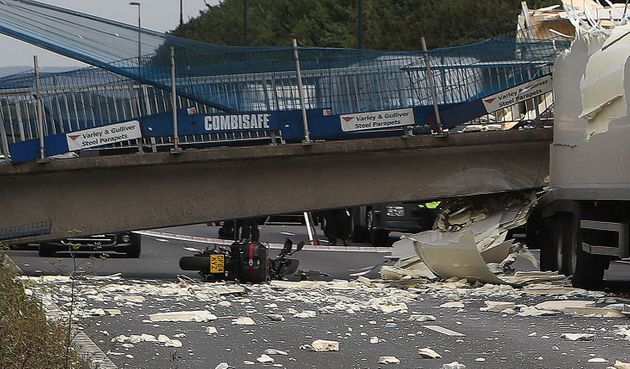 Amotorcycle lies on the ground underthecollapsed bridge on the M20.The ridertold...