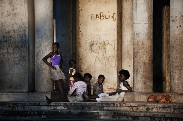 Mozambican children from Beira enjoy the sunset as they sit on the main entrance of the Grand hotel Beira on November 2, 2010