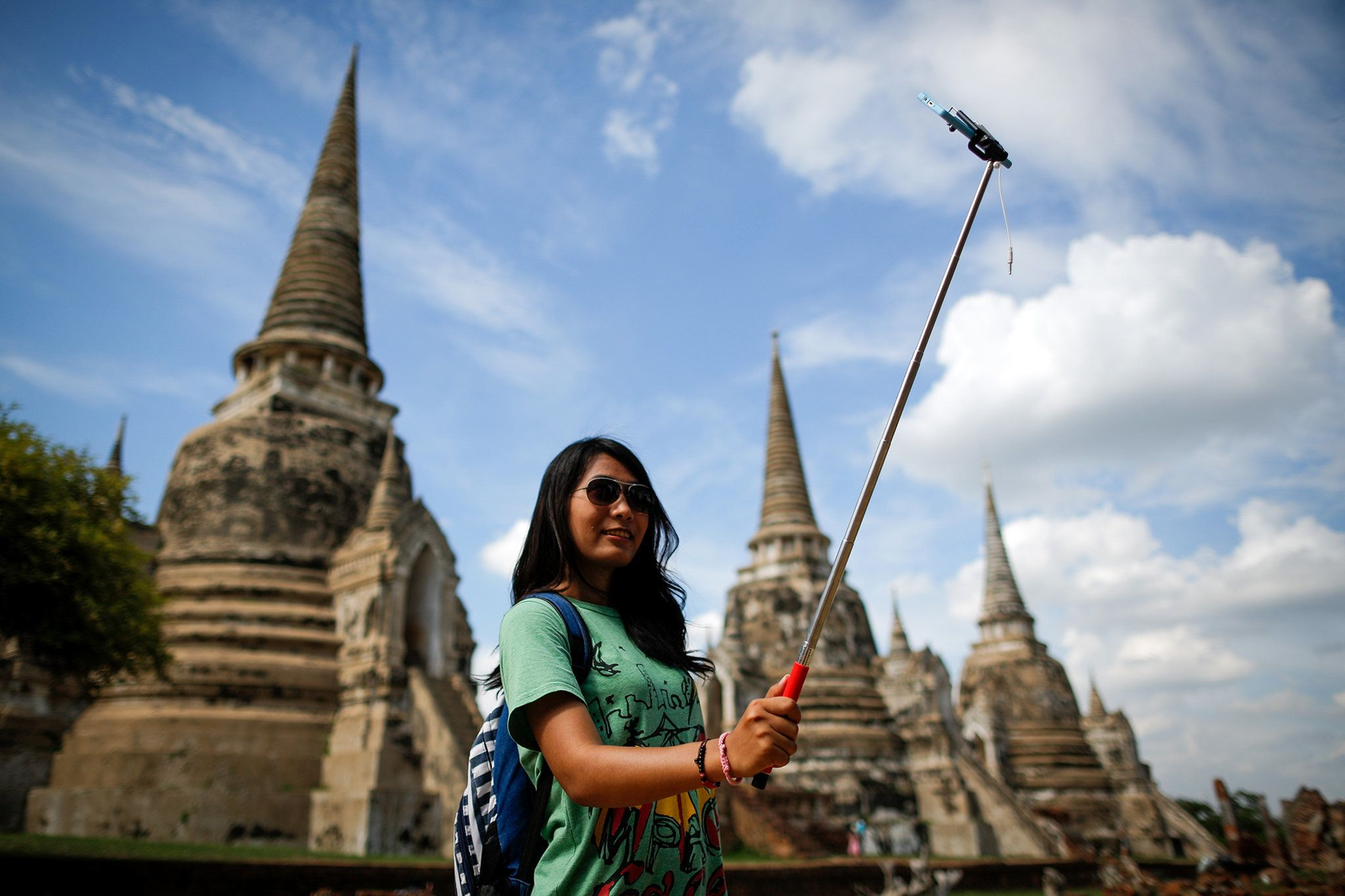 A tourist snaps a picture of herself with a selfie stick at Wat Phra Sri Sanphet, a temple in the ancient city of Ayutthaya, Thailand.
