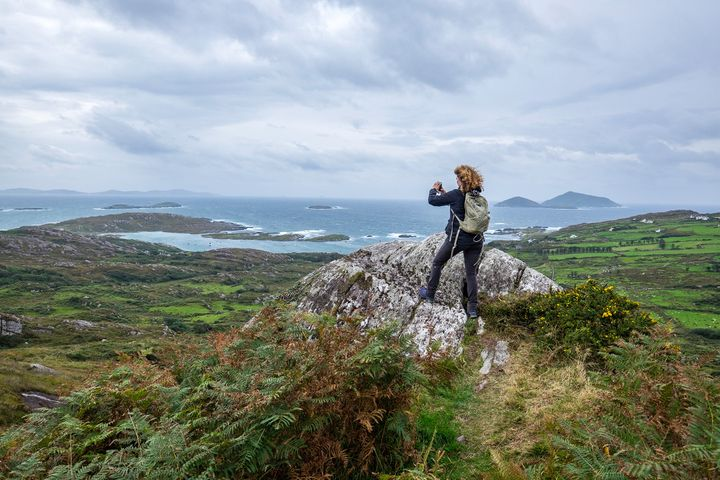 A woman snaps a photograph while hiking in the Beara Peninsula, Ireland.