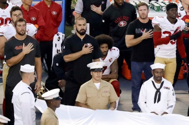Colin Kaepernick (middle) kneels alone during the US national anthem.