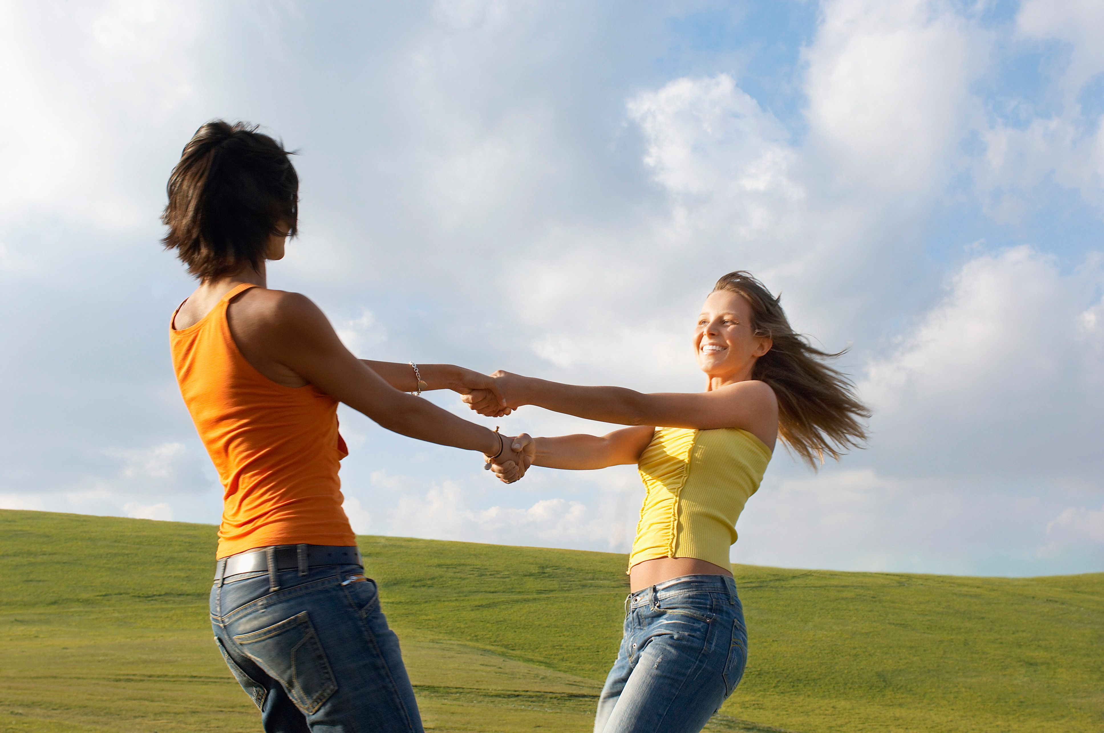 Two young swinging each other around in mountain field side view
