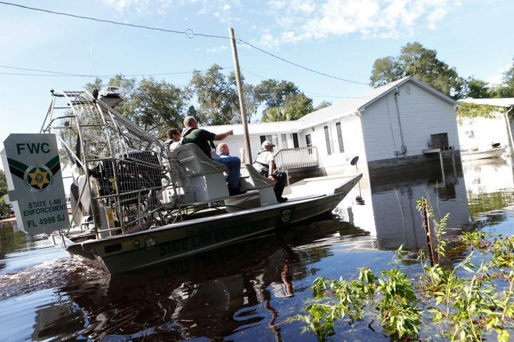 Law enforcement officers use an airboat to survey damage around homes from high winds and storm surge associated with Hurrica