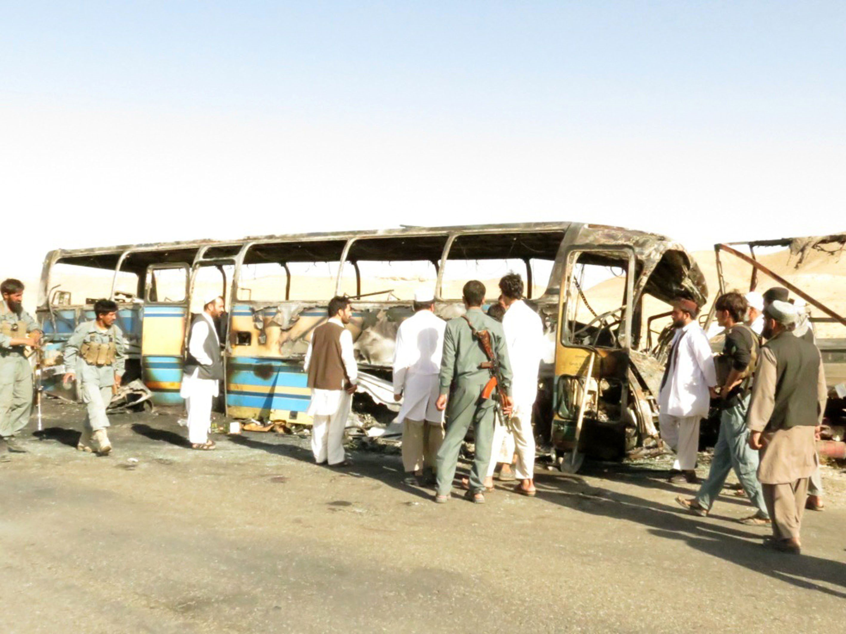 Security forces and civilians inspect the wreckage of a damaged bus after it collided with a lorry in Zabul, Afghanistan on S