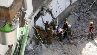 Israeli medics and emergency units carry a wounded person away on a stretcher from a construction site after an underground car park collapsed on September 5, 2016 in the Ramat Hahayal neighbourhood in the coastal city of Tel Aviv. Police reported at least one person dead. Ramat Hahayal is home to a number of high-tech offices in Israel's booming technology industry, based around the city of more than 400,000 people.   / AFP / GIL COHEN-MAGEN        (Photo credit should read GIL COHEN-MAGEN/AFP/Getty Images)