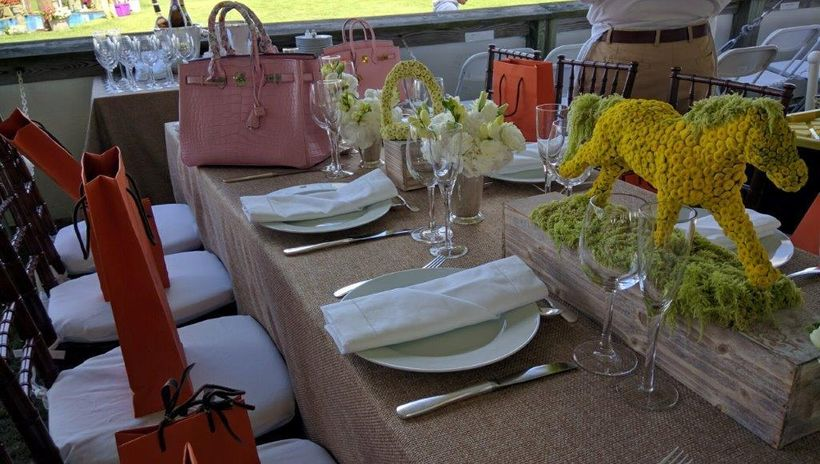Table by Hermes featured Birkin bags and bright orange shopping bags