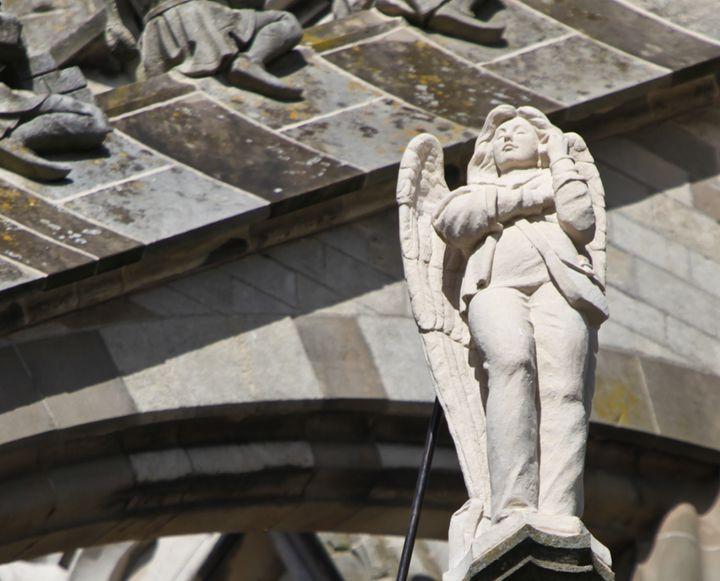 An angel on his/her cell phone on one of the flying buttresses of St John's Cathedral, Den Bosch, Netherlands.
