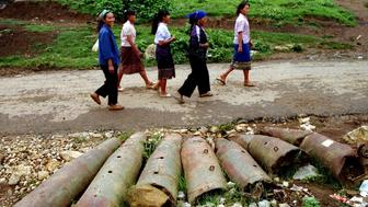 Laotian women walk past bombs and shells lie on the streets in this northern province. From 1964-1973, US planes dropped two million tonnes of bombs in Laos, many of them unexploded, still scattered throughout the countryside causing casualties to the Laotian people