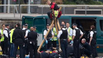 Emergency services surround protestors from the movement Black Lives Matter after they locked themselves to a tripod on the runway at London City Airport in London on September 6, 2016. Flights at London City Airport have been delayed after Black Lives Matter protesters crossed the dock and 'occupied' the runway. / AFP / DANIEL LEAL-OLIVAS        (Photo credit should read DANIEL LEAL-OLIVAS/AFP/Getty Images)