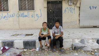JARABLUS, SYRIA - AUGUST 31: Boys sit in front of their homes in the border town of Jarablus, August 31, 2016, Syria. Turkish troops and Turkey-backed rebels have been fighting Kurdish-led forces and IS since Turkey's incursion into Syria on Aug. 24. with the swift capture of Jarablus, a town a few km inside Syria that was held by Islamic State.(Photo by Defne Karadeniz/Getty Images)