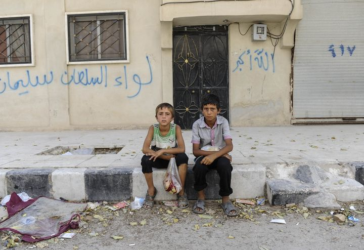 JARABLUS, SYRIA - AUGUST 31: Boys sit in front of their homes in the border town of Jarablus, August 31, 2016, Syria. Turkish