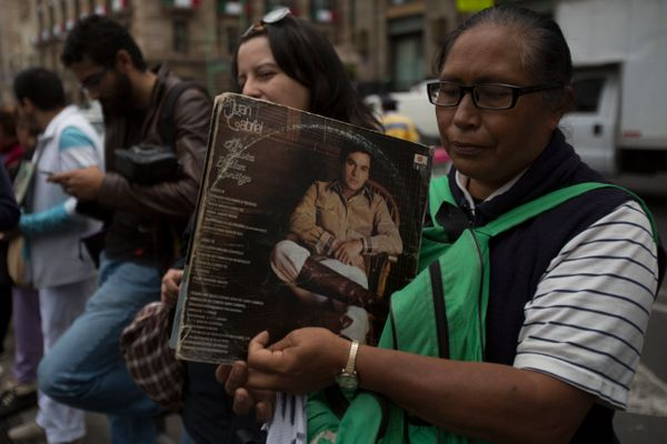 A woman holds the records of Mexican songwriter and singer Juan Gabriel during the Memorial at Palacio de Bellas Artes.
