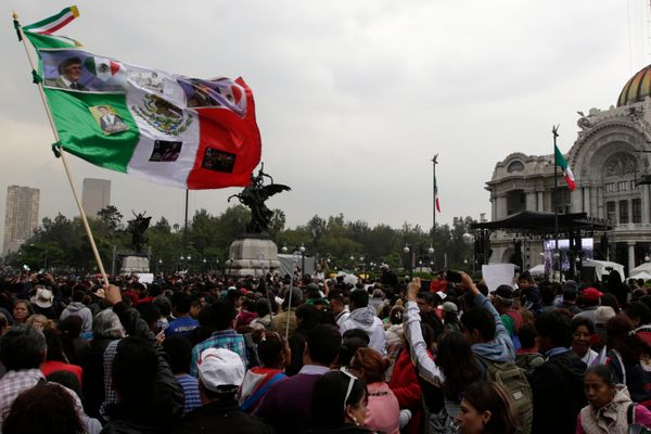 A man waves a Mexican flag with photographs of Mexican singer Juan Gabriel during the Memorial at Palacio de Bellas Artes.