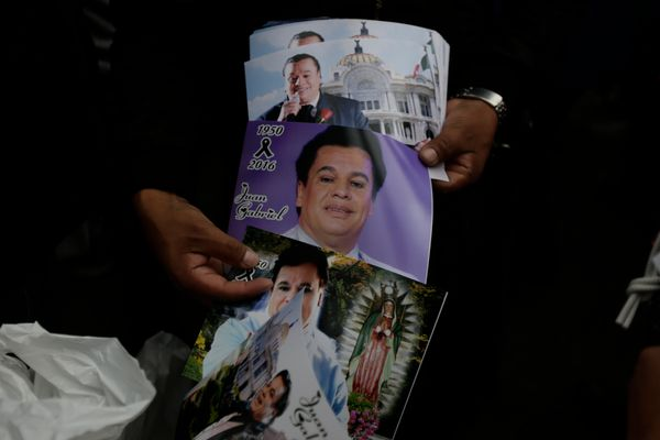 People hold photos of Mexican songwriter and singer Juan Gabriel during the Memorial at Palacio de Bellas Artes.