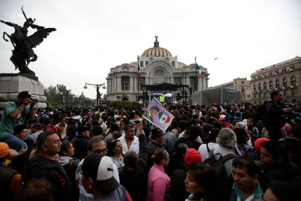 People stand outside the Palacio de Bellas Artes during the Memorial of Mexican singer Juan Gabriel.