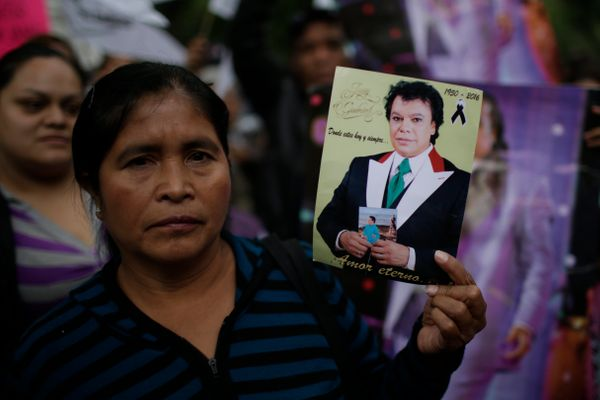 A woman holds an image of Mexican songwriter and singer Juan Gabriel during the Memorial at Palacio de Bellas Artes.