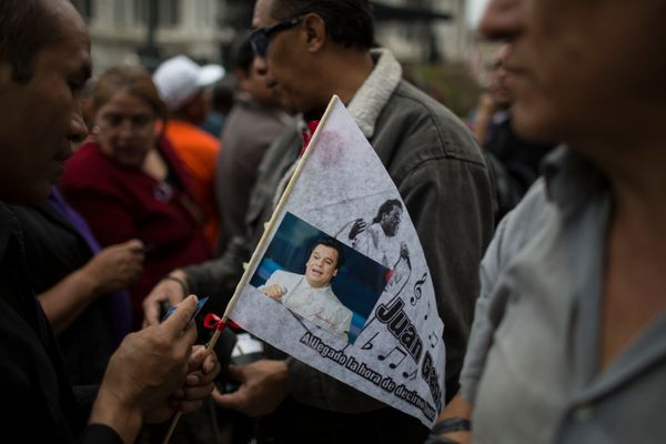 A man holds a picture of Mexican songwriter and singer Juan Gabriel during the Memorial at Palacio de Bellas Artes.