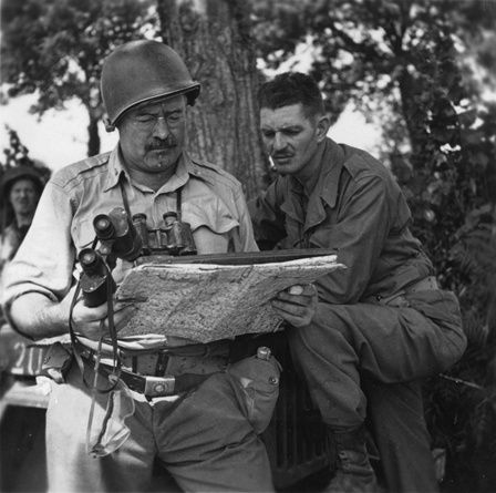 <strong></strong>Ernest Hemingway looking at a map with a soldier during World War II, circa 1944.