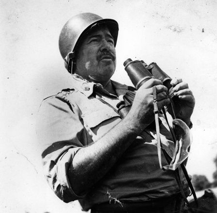 Ernest Hemingway in uniform, wearing a helmet, and holding binoculars during World War II, circa 1944.