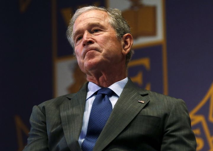 Former U.S. President George W. Bush listens to a speech while visiting Warren Easton Charter High School one day before the