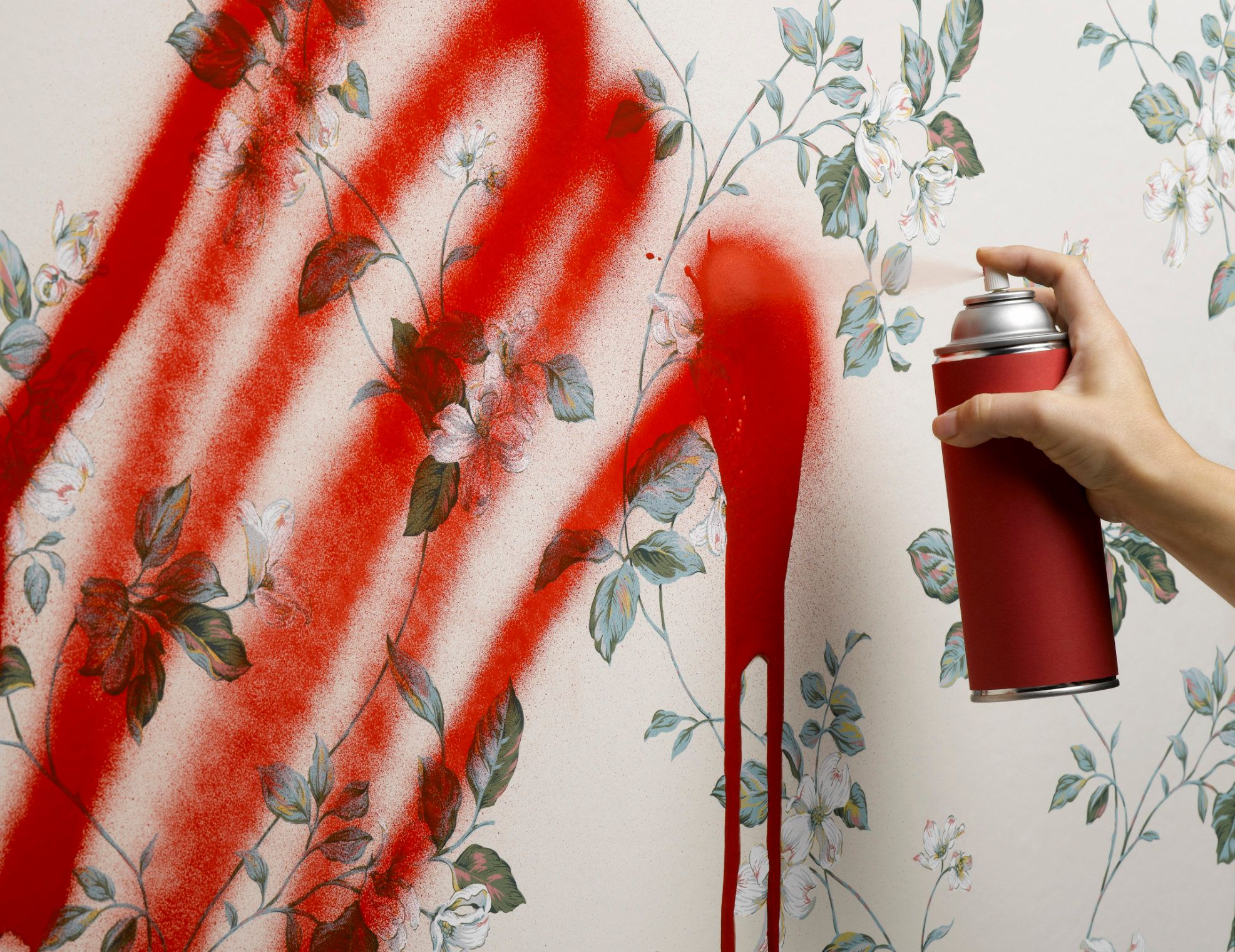 Female hand spray painting wallpaper