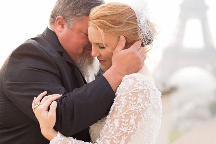 In this 2015 photo, Tim Buchanan is seen hugging his wife, Jeni, in Paris. Buchanandied of a heart attack on Sept. 3 at his daughter's wedding right after the father-daughter dance.