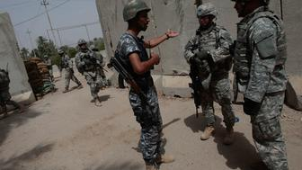 BAGHDAD, IRAQ - JUNE 20:  Lt. Col. Jim Crider of 1st Squad, 4th Cavalry Regiment of the 1st Infantry Division (C) and his interpreter (R) talk to an Iraqi police member about a recent insurgent attack at the Iraqis base in the tense Dora neighborhood June 20, 2007 in Baghdad, Iraq.  Lt. Col. Crider canvases his area frequently, overlooking the efforts of his officers and attempting to get to know the residents and find insurgents. The soldiers of 1-4 Cav patrol Dora, a neighborhood in south Baghdad that's mostly Sunni Muslim and has been a hotbed of the insurgency for years.  (Photo by Chris Hondros/Getty Images)