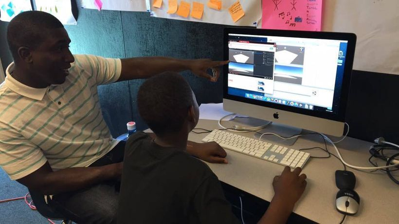 <i>Stanford Ph.D. candidate and lead instructor Kareem Edouard discussing design methodology while his student uses one monit