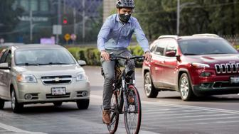 A man rides a bicycle next to traffic along the Paseo de la Reforma in Mexico City, Mexico, on Wednesday, Aug. 10, 2016. Mexico's push to reduce air pollution may set the stage for a surge in clean energy-related bond sales. For the first time, the government will auction $8 billion worth of clean energy projects this year, according to Pricewaterhouse Cooper. Photographer: Brett Gundlock/Bloomberg via Getty Images
