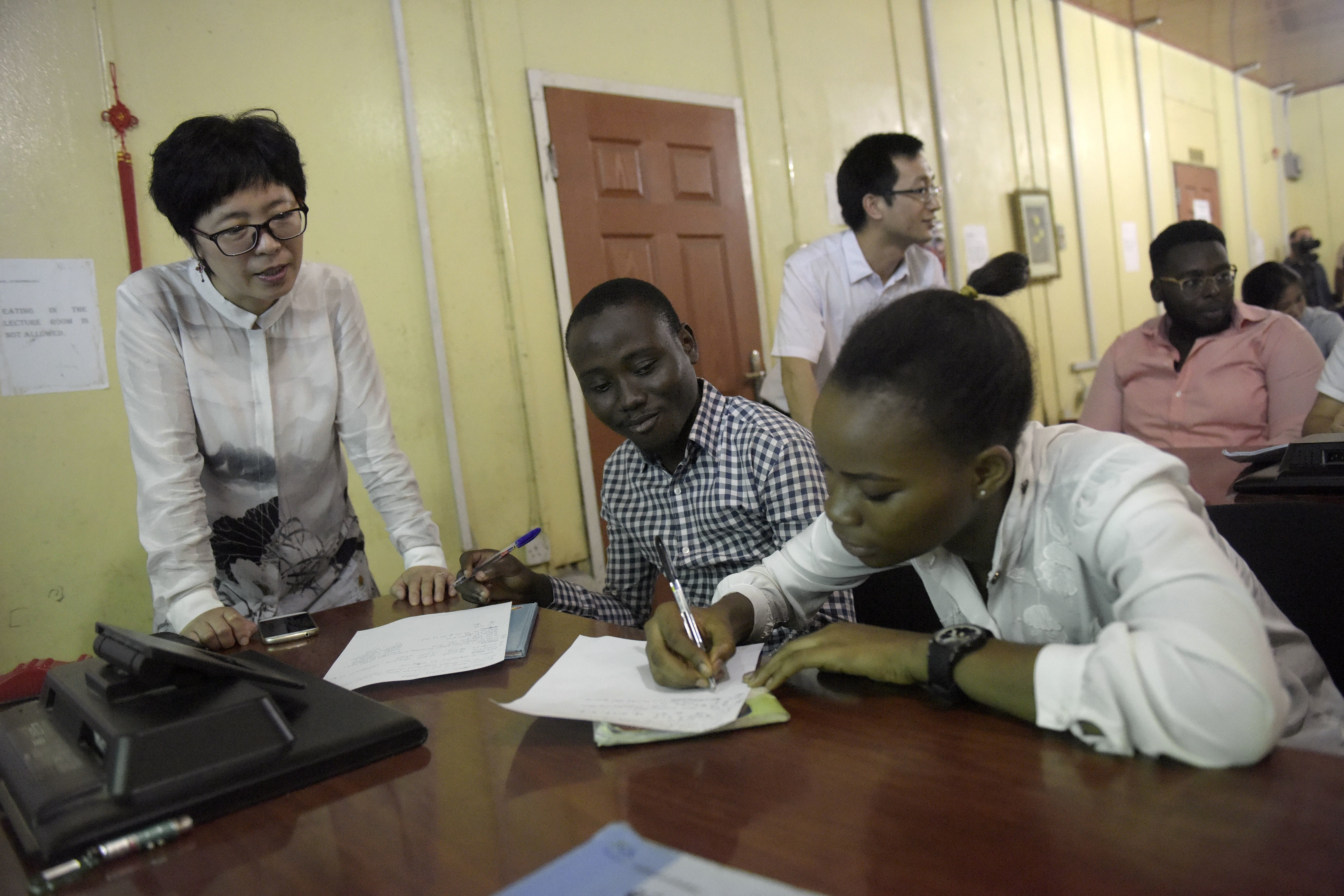 Yongjin Wang, director of the Confucius Institute, looks at students writing in Chinese at the Confucius Institute at the University of Lagos on April 6, 2016.   Some three dozen Nigerians are currently studying for language and culture degrees at Chinese universities while a second Confucius Institute has been opened in southeast Nigeria. Lagos has five pilot project schools where Mandarin is taught.  / AFP / PIUS UTOMI EKPEI        (Photo credit should read PIUS UTOMI EKPEI/AFP/Getty Images)