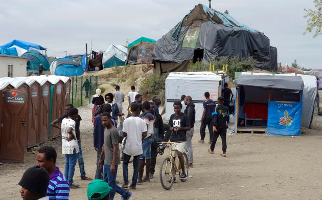 Migrants walk in the northern area of the camp called the