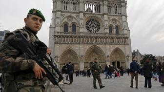 Armed soldiers patrol in front of the Notre Dame Cathedral, as part of heightened security measures ahead of Christmas, in Paris, France December 20, 2015.  REUTERS/Jacky Naegelen