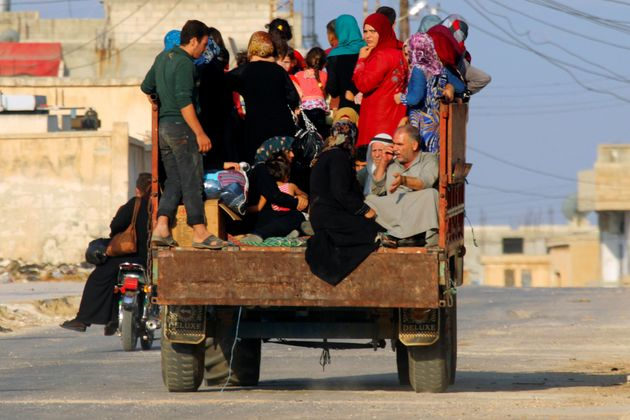 Civilians sit on a pick-up truck with their belongings in Taybat al Imam town after rebel fighters from...