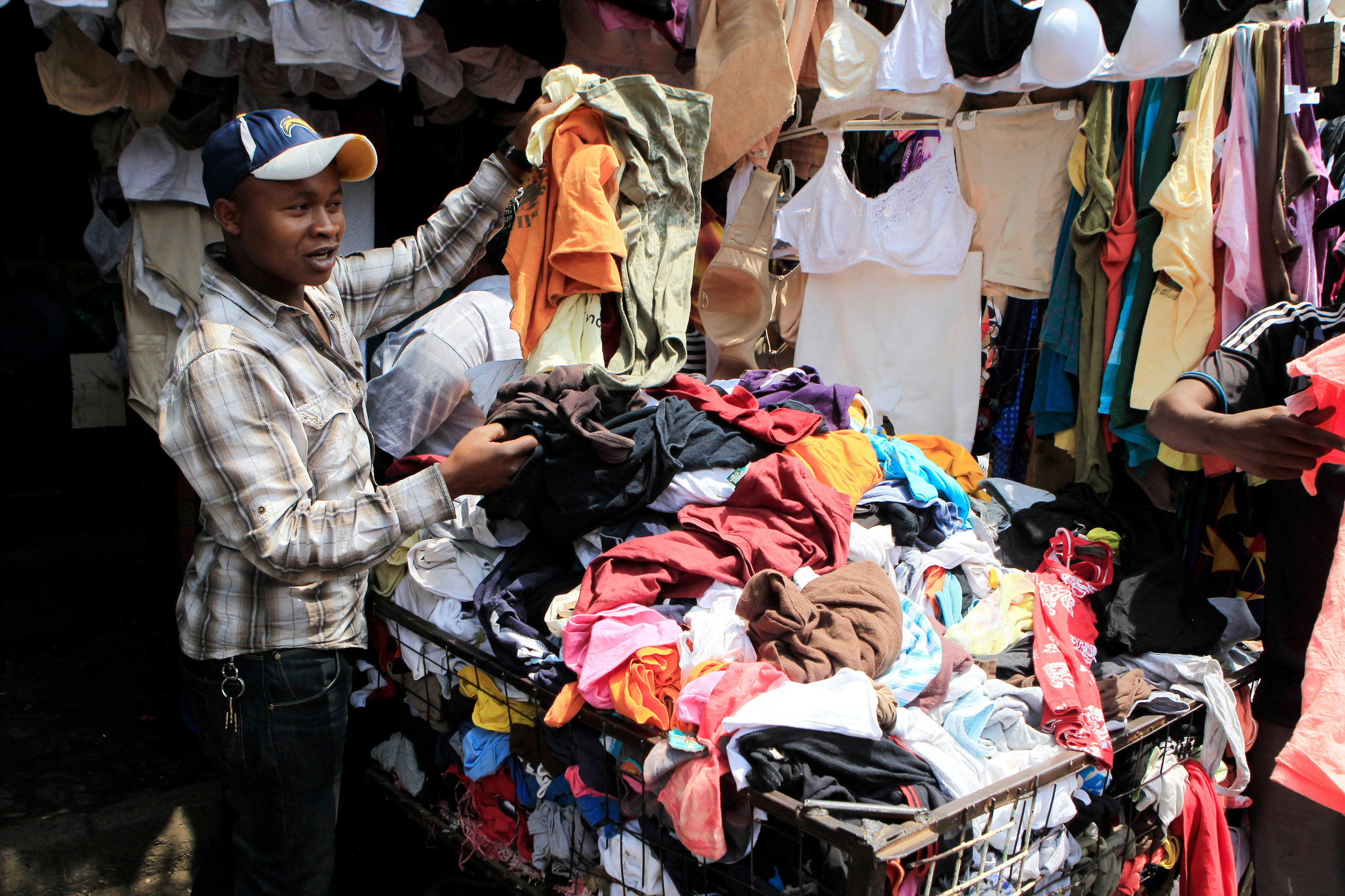 A vendor sells secondhand cloths at a stall in the busy Gikomba market in Nairobi, Kenya, Sept. 18, 2014. Shaded by ragged sq