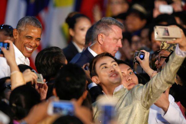 Attendees take selfies as Obama departs.