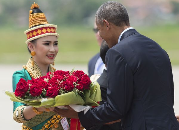 Obama receives flowers after arrivingon Air Force One in Luang Prabang.